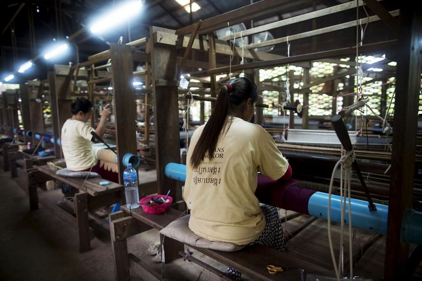 Weavers operate wooden handlooms to produce silk at a mill in Siem Reap, Cambodia, on June 27, 2015.
