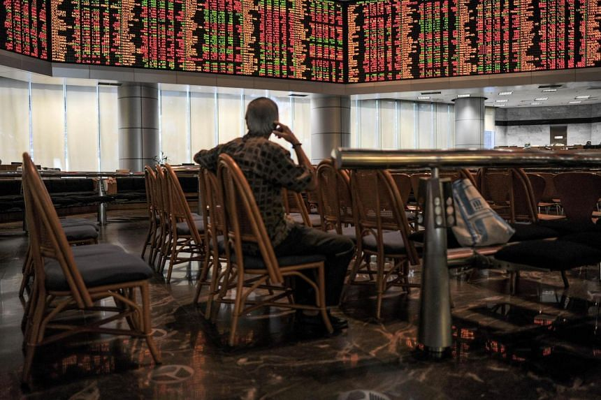 A man looking at electronic display boards at the Malaysia Stock Exchange in Kuala Lumpur.
