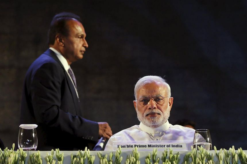 India's Prime Minister Narendra Modi attends the launch of Digital India Week as Anil Ambani (L), chairman of the Reliance Anil Dhirubhai Ambani Group, stands behind him in New Delhi, India, July 1, 2015. India is reinvigorating an US$18 billion camp