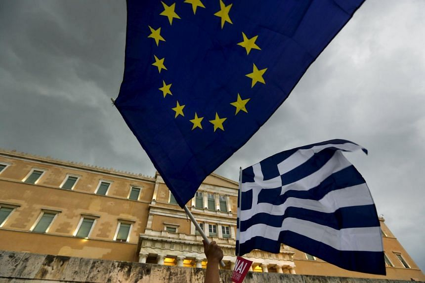 Protesters waving Greek and European Union flags during a pro-Euro rally in front of the parliament building in Athens.