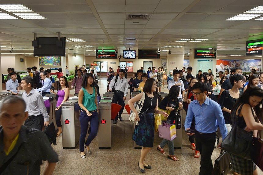 People at the Raffles Place MRT station gantry.