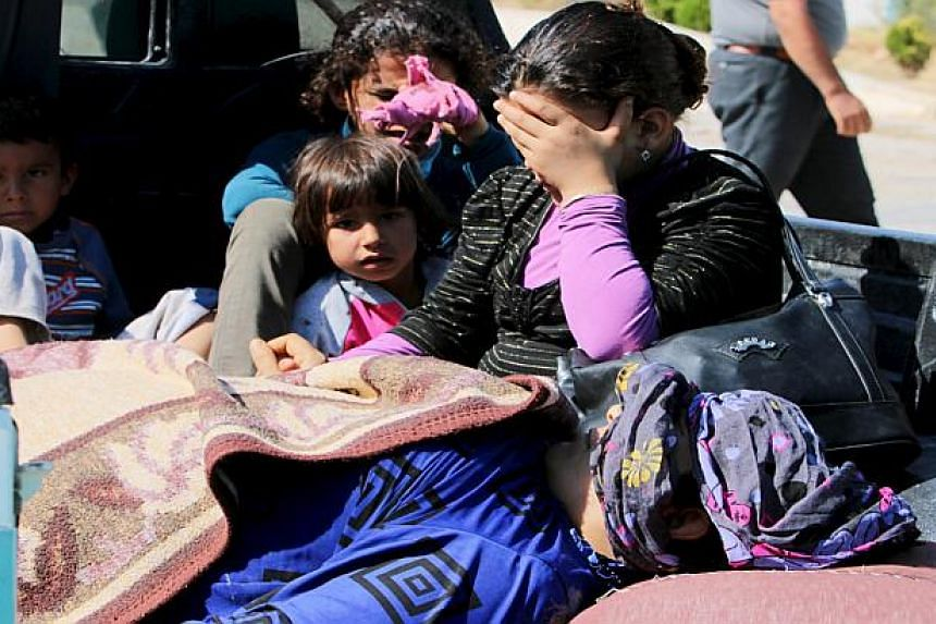 Civilians fleeing Islamic State in Syria wait to cross into Turkey.