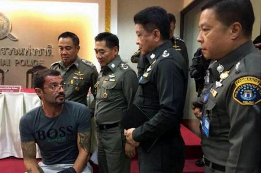 Xavier Andre Justo (seated) appearing before the media after being arrested in Thailand.