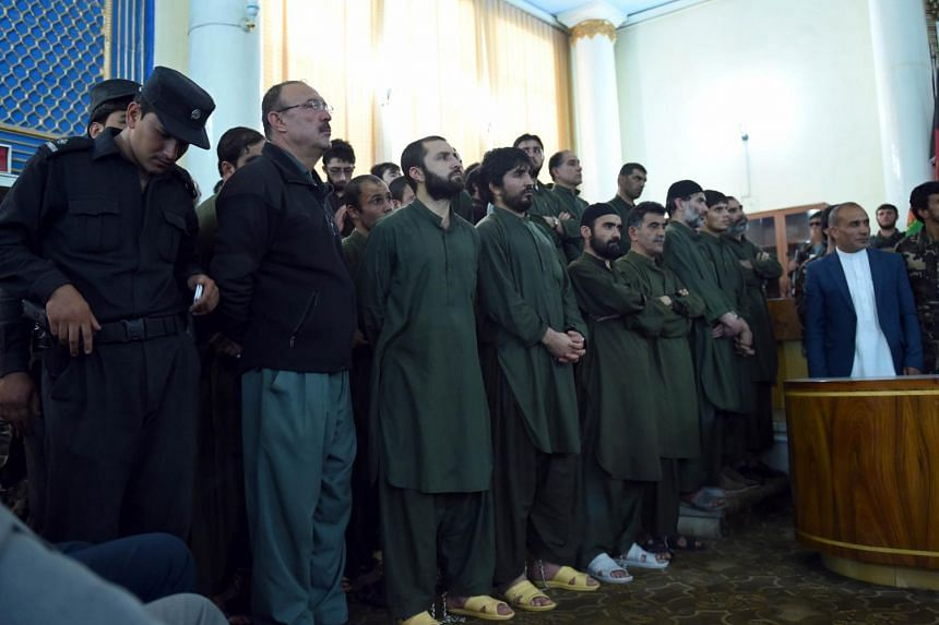 Suspects stand before a judge during a primary court trial in Kabul on May 2, 2015.