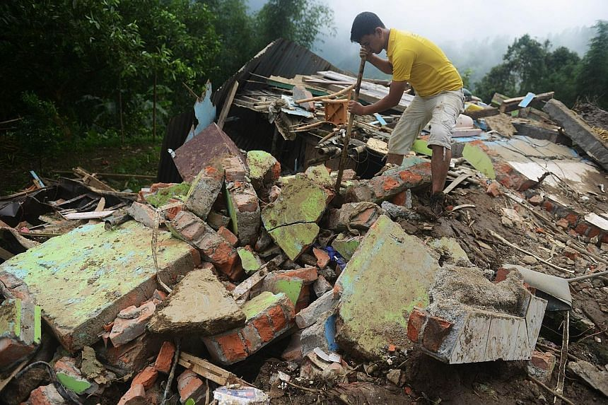 A man searching for the bodies of those killed in a landslide at Tingling village, near Mirik, some 60km from Siliguri, yesterday. Landslides triggered by heavy rain have killed at least 21 people across India's famed tea-growing region of Darjeeling