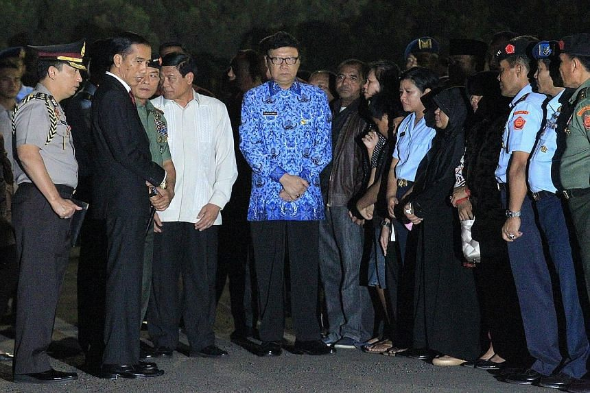 (Above) A relative of a plane crash victim grieves at a military airbase in Medan. Officials said there were 122 people on the flight, more than the 113 initially reported. Most were servicemen and their families. (Left, above) Indonesian President J
