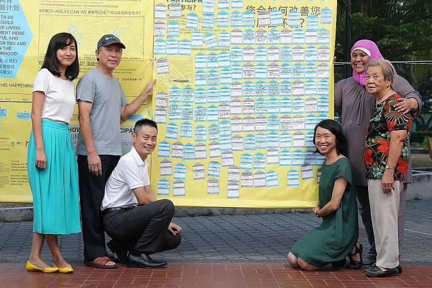 Participate in Design founders Mizah Rahman (left) and Jan Lim (third from right), with Tampines Changkat residents (from left) Tan King How, Chong Kok Yeow, Suzana Ahmad and Liew Fook Wu, with a canvas board displaying the written views of residents