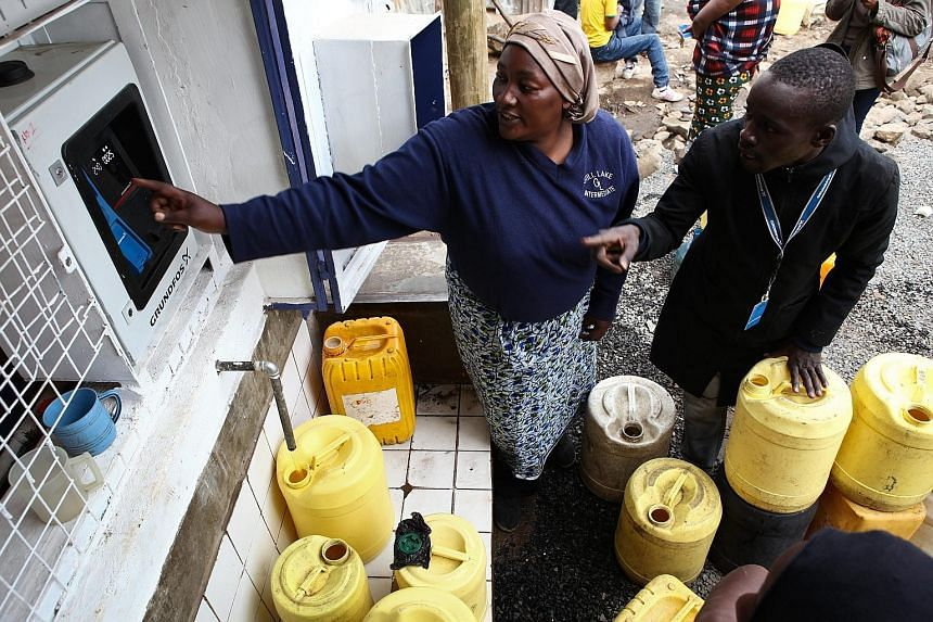A resident of the Mathare slums in Nairobi (left) getting some help in buying clean water from an ATM-style water dispenser last week. The clean water from such dispensers is cheaper than what other water vendors used to charge for water that was oft