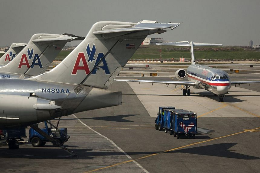 An American Airlines plane taxis past other American Airlines McConnell Douglas MD-82 planes standing by gates at LaGuardia Airport in New York.