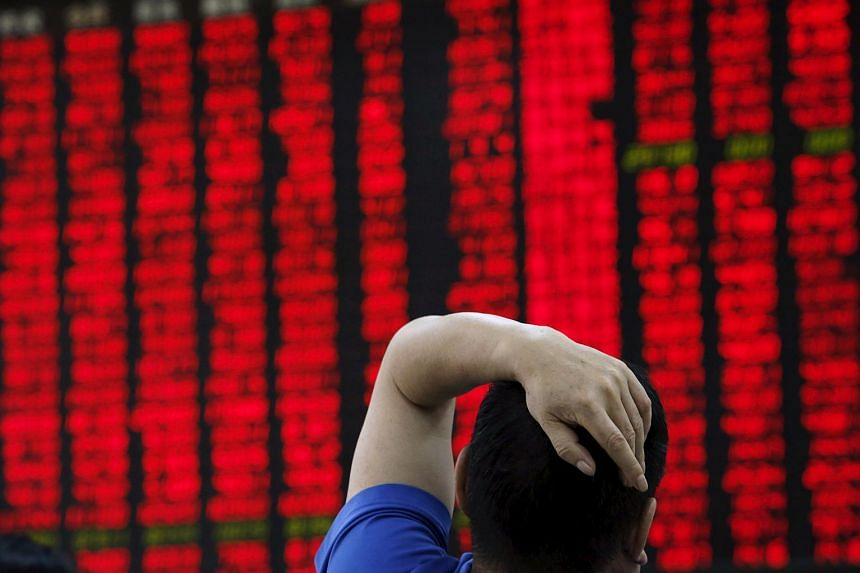 A man watching a board showing stock prices at a brokerage office in Beijing, China.