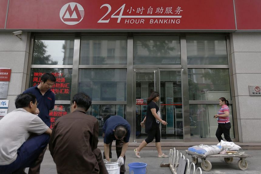 People walk in front of a Chinese bank branch in Beijing, China, on June 25, 2015.