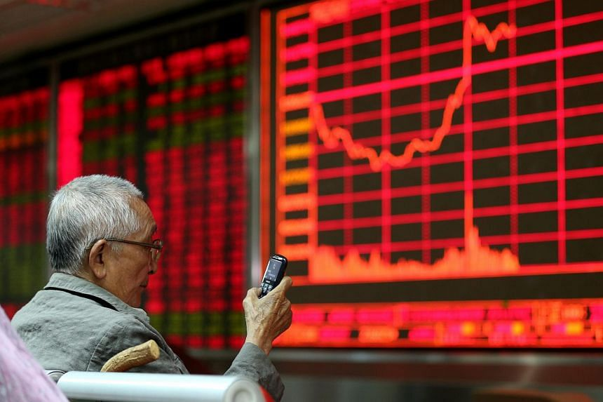 A man sits in front of an electronic screen at a brokerage firm in Beijing, China.