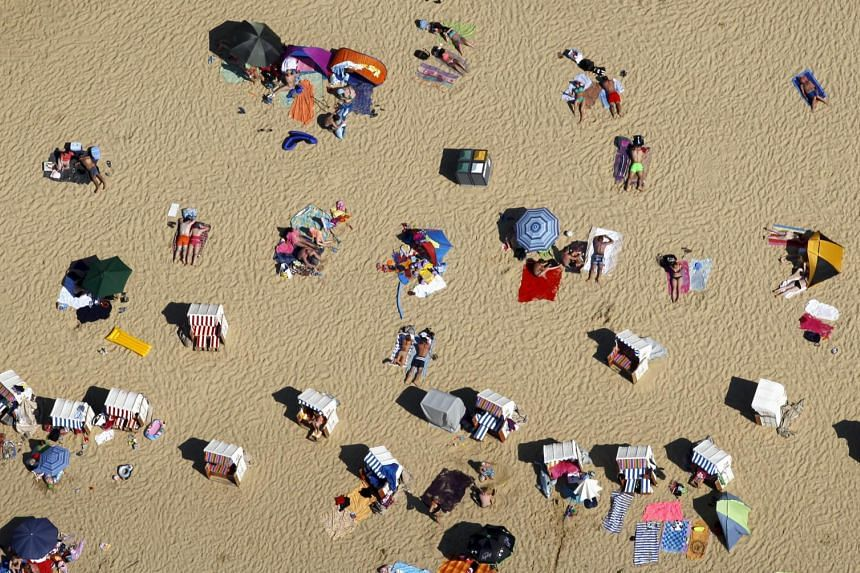 People relax on the shores of Silbersee lake in Haltern, Germany.