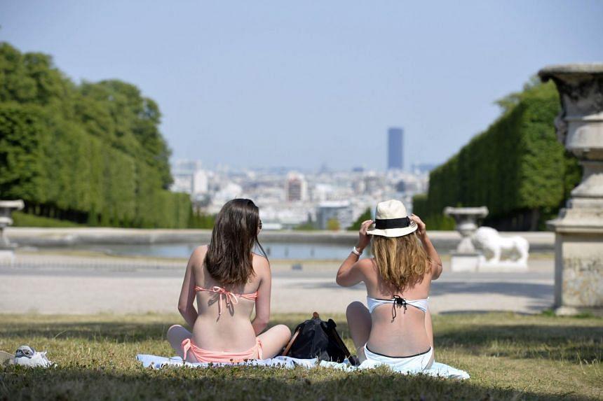 Women in bikinis sunbathe on the grass in a park in Saint-Cloud, west of Paris.