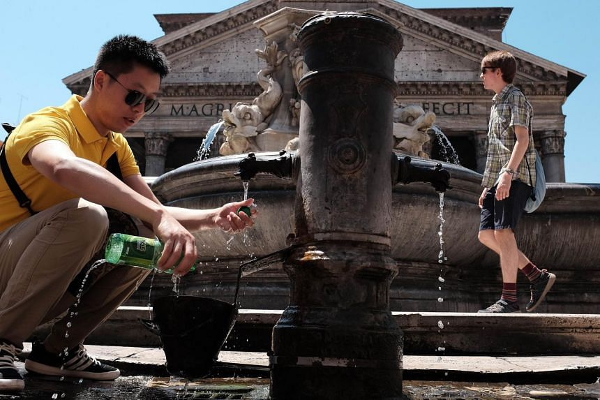 A man fills up his bottle with water in Rome.