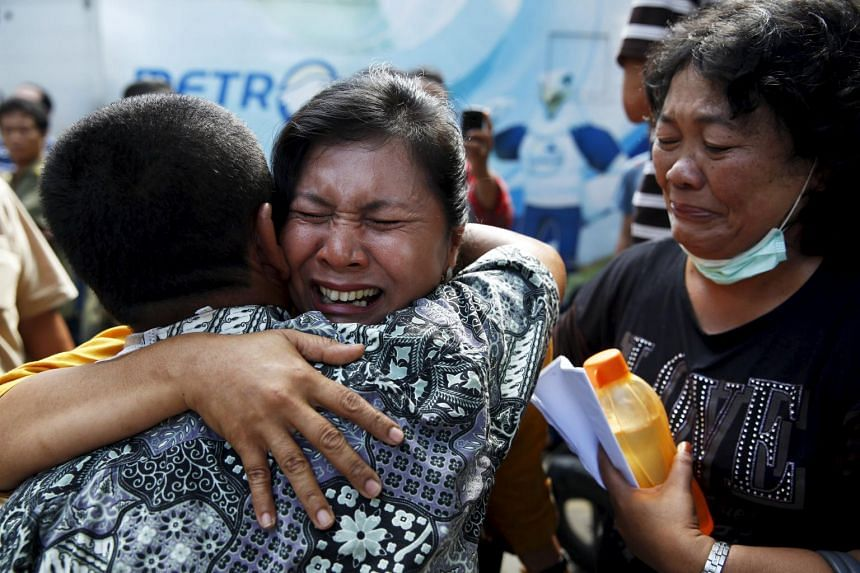 A woman cries after confirming that her brother was among the victims of the Indonesian military plane that crashed into a residential area, in Medan, Indonesia, on July 2, 2015.