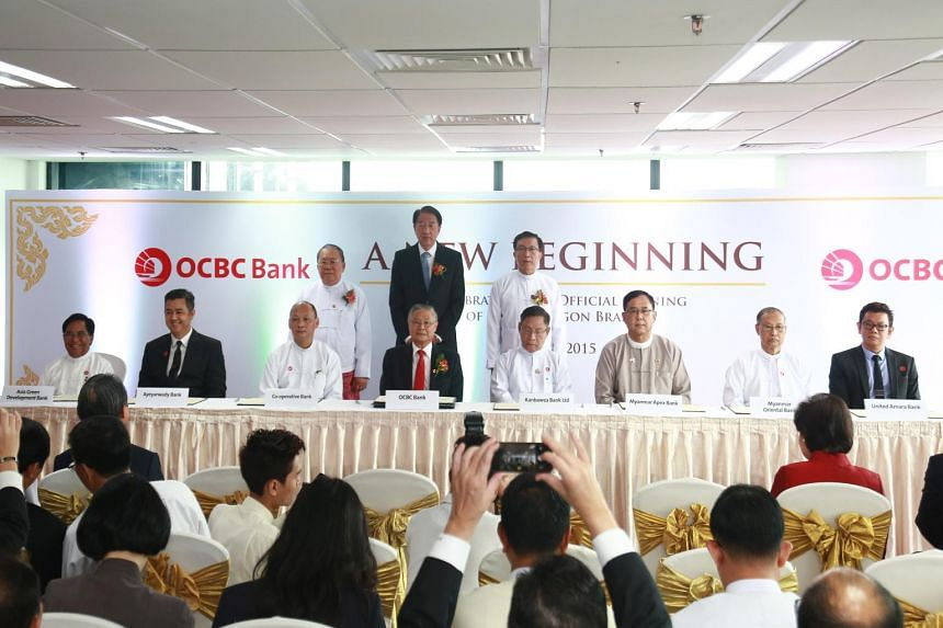 DPM Teo (centre, back) and officials during the signing of MOUs at the opening of OCBC Yangon Branch.