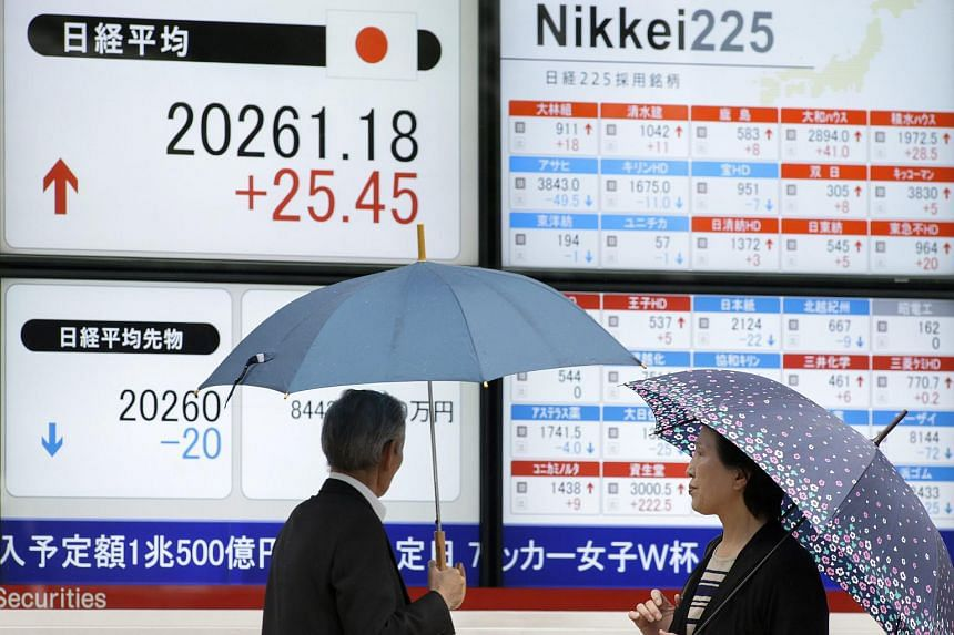 Pedestrians looking at the Tokyo's Nikkei Stock Average and 225-issue Tokyo stock index.