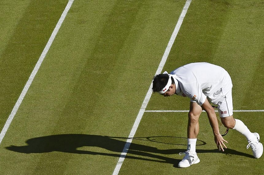 Kei Nishikori wearing strapping on his calf, stumbles as he stretches for a shot during his match at the 2015 Wimbledon Tennis Championships.