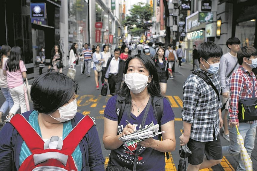Chinese tourist wearing masks to prevent contracting Middle East Respiratory Syndrome (Mers) walk at the Myeongdong shopping district in central Seoul.