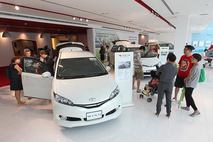 Potential car buyers and members of the public at a Toyota showroom.