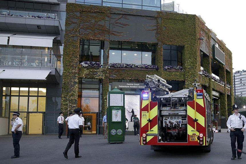 Police evacuating the area as a fire engine arrives after a fire broke out inside Centre Court in Wimbledon.
