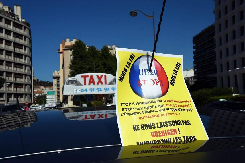 "A taxi displaying a poster that reads, ""Stop Uber"", during a protest in the city of Marseille, France."