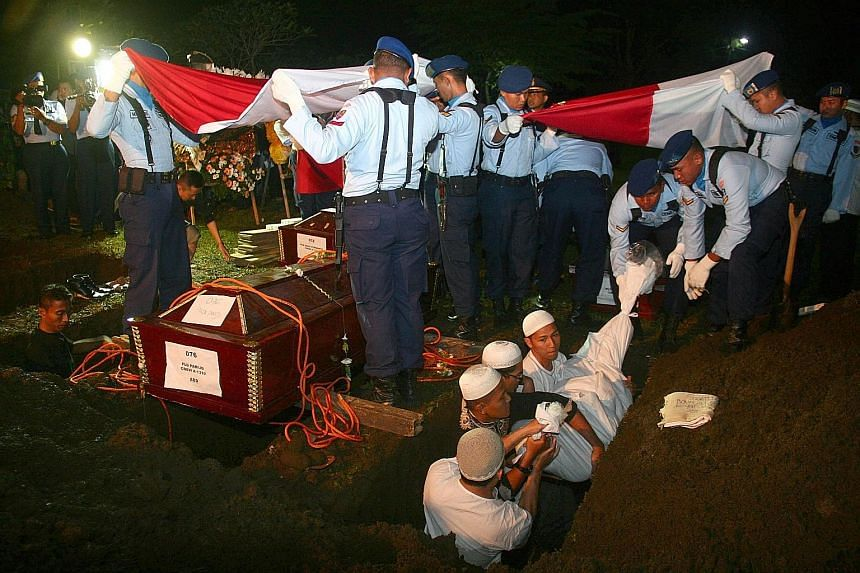 LEFT: Soldiers and police personnel clearing debris at the crash site in Medan yesterday. BELOW: Victims of the plane crash, who include relatives of soldiers and military officers, being buried in a public cemetery following a military ceremony in M