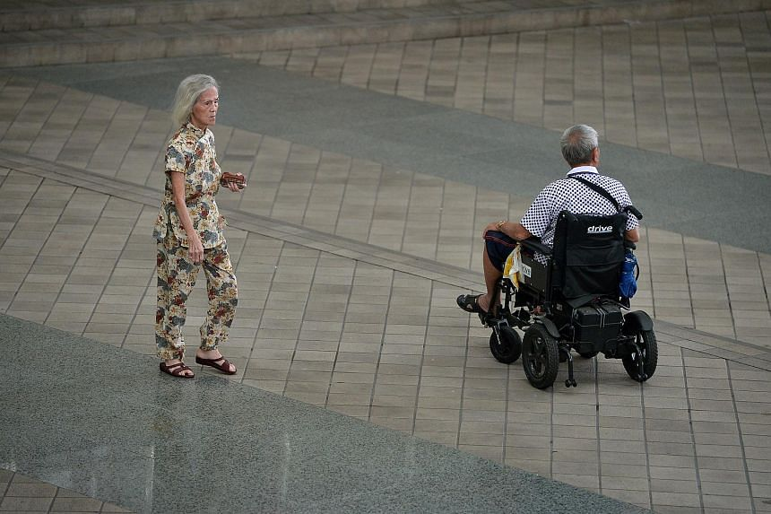 An elderly man on a wheelchair and an elderly woman.