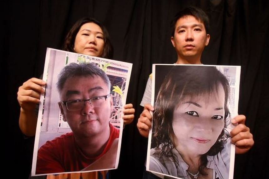 Mrs Chan Wai See (left) and Mr Chung Chin Lung hold up pictures of hostages Mr Bernard Then Ted Fun (left) and Ms Thien Nyuk Fun.