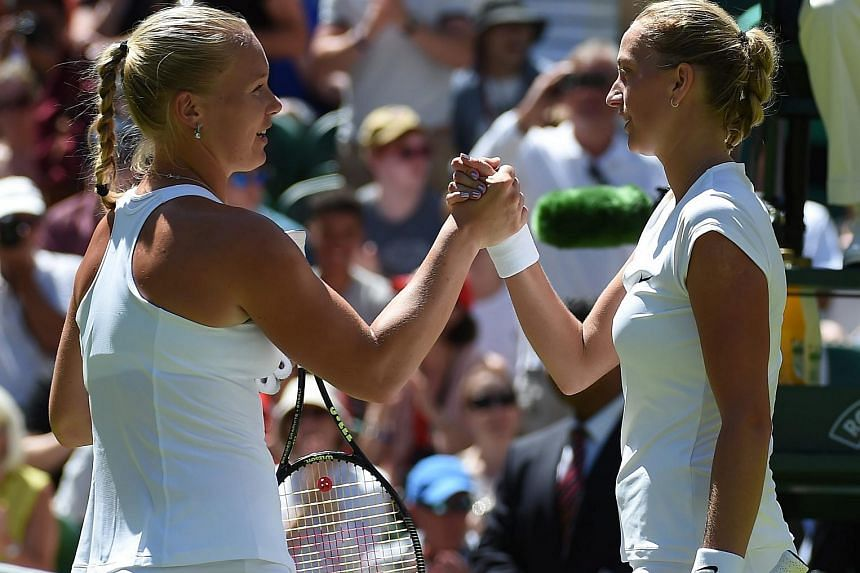 Petra Kvitova of the Czech Republic (right) at the net with Kiki Bertens of the Netherlands whom she defeated in their first round match at the Wimbledon Championships in London on June 30, 2015.