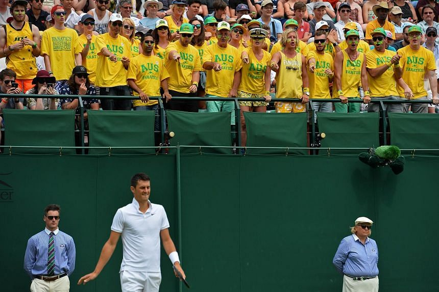 Australian fans gesture towards Australia's Bernard Tomic as they sing during his men's singles second round match against France's Pierre-Hugues Herbert at the 2015 Wimbledon Championships in London, on July 1, 2015.