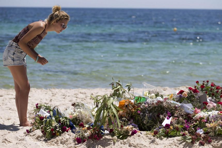 A British tourist lays flowers at the site of the attack on June 30, 2015.
