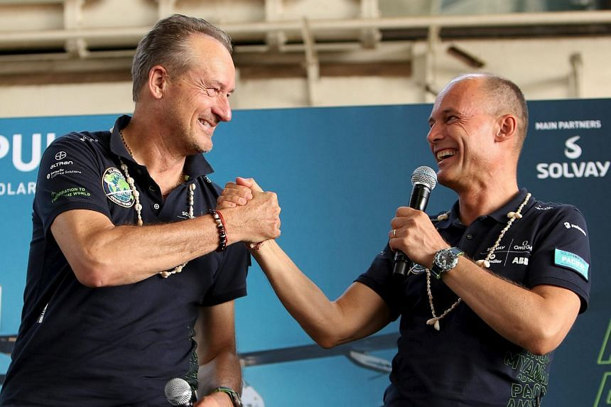 Pilot Andre Borschberg (left) and Bertrand Piccard congratulating each other at a news conference after the Solar Impulse 2 airplane landed at Kalaeloa airport.