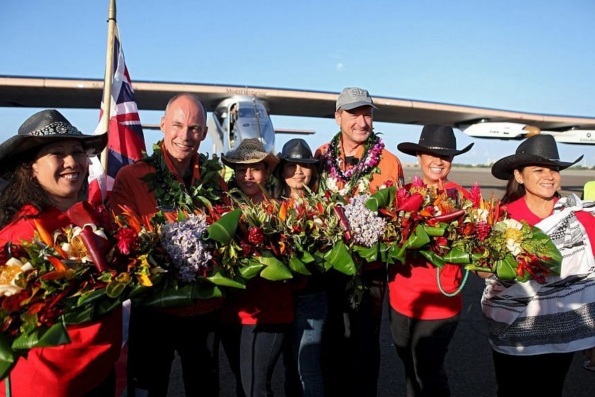 Pilots Bertrand Piccard (second from left) and Andre Borschberg (third from right) are presented with floral leis by Hawaiian Pa'u riders.
