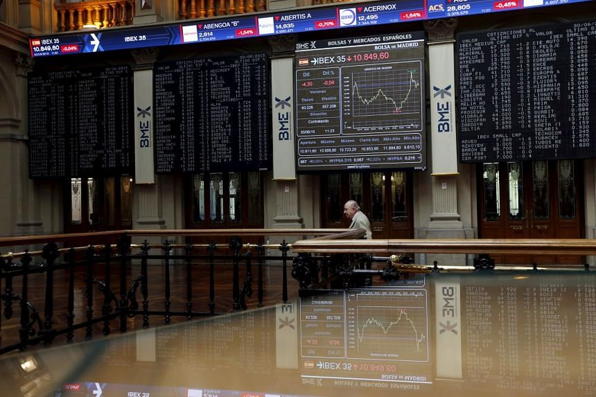 A trader walks next to a displays showing market indices at Madrid's bourse, Spain, June 30, 2015.