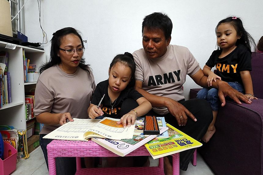 Madam Siti Zubaidah, 41 (left), sends her daughter Amelia Shasmeen Azman, five (second from left), for English phonics and reading classes as well as weekly abacus lessons. With them are Amelia's father, Mr Azman Rahmad, 50, and her sister Alisha Mia