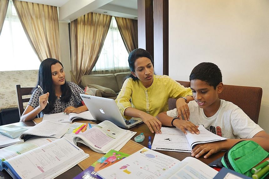Madam Sujata Devi (centre) with her daughter Annushiyaa (left) and son Anirudh at home. The fees for their tuition lessons add up to over $1,500 a month, up from about $700 last year.