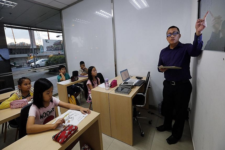 Maths tutor Diaz Adi Utama, 27, teaching a class. Parents often find it necessary to send their children for tuition in maths, especially at the higher levels, because the subject is too technically taxing for them to coach personally.