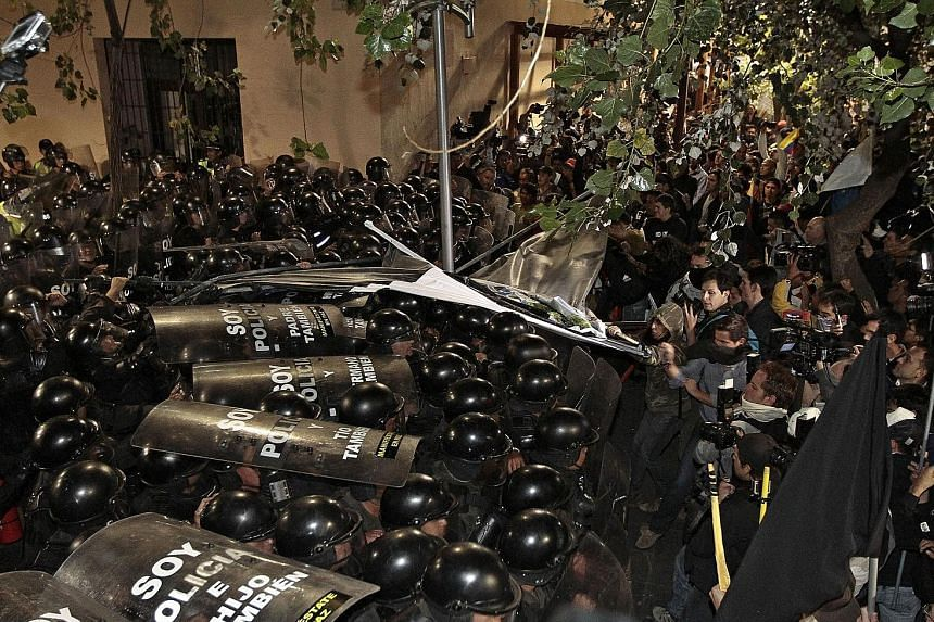 Opponents of Ecuadorean President Rafael Correa clashing with riot policemen in Quito. Three days before the arrival of Pope Francis in Quito, thousands demonstrated for and against Mr Correa on Thursday. Mr Correa, who has been hounded by protests d