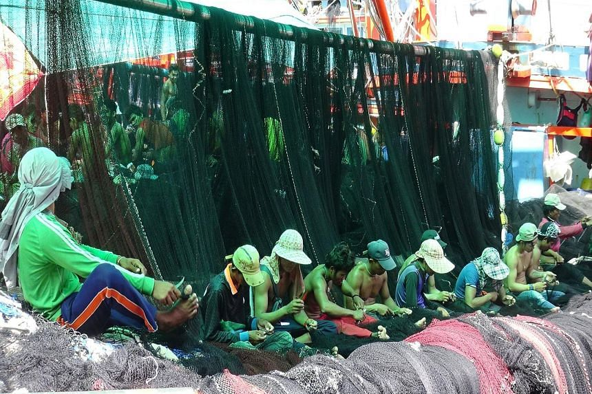 Migrant workers (above) sorting fish at a port in Mahachai, on the outskirts of Bangkok. Workers repairing fishing nets for trawlers (left) in Rayong province yesterday.