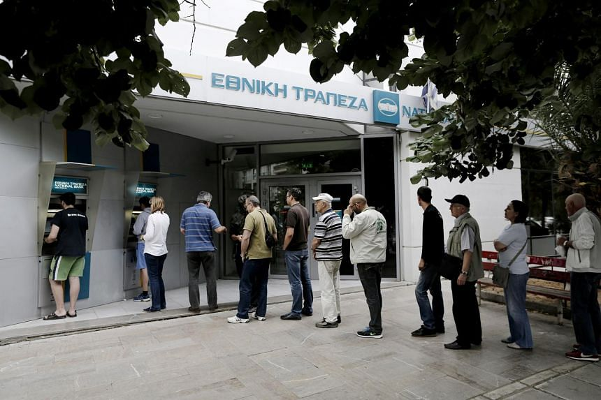 Customers queue to use an ATM in Thessaloniki, Greece.