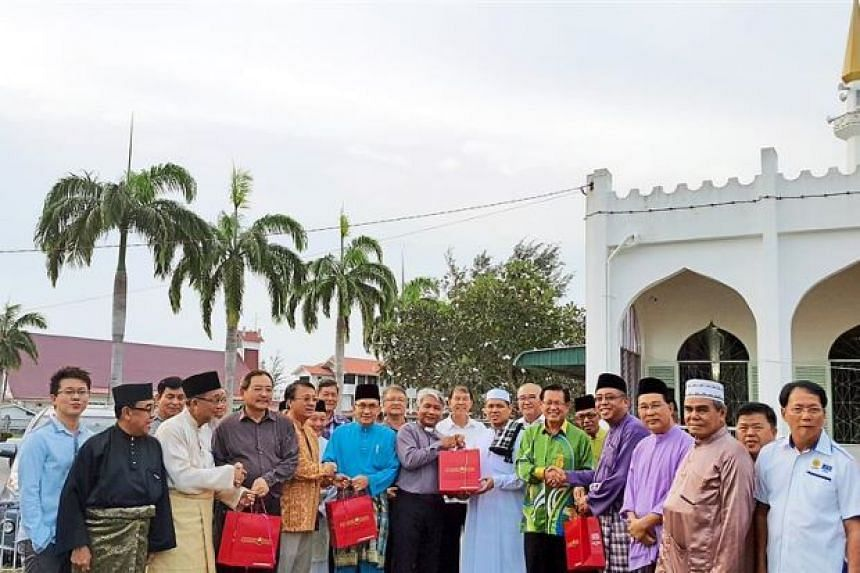Mosque and church leaders exchanging goodies in front of the Good Shepherd Church (with red roof) and An-Naim Mosque in Sarawak.