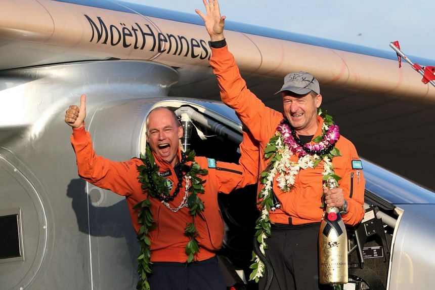 Bertrand Piccard (left) celebrates with Andre Borschberg after the Solar Impulse 2 plane, piloted by Borschberg, lands at Kalaeloa airport.