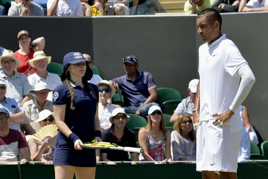 Nick Kyrgios showing his playful nature, dropping his racket and standing frozen to the spot with a look of mock confusion, even as the ball girl hands it back.