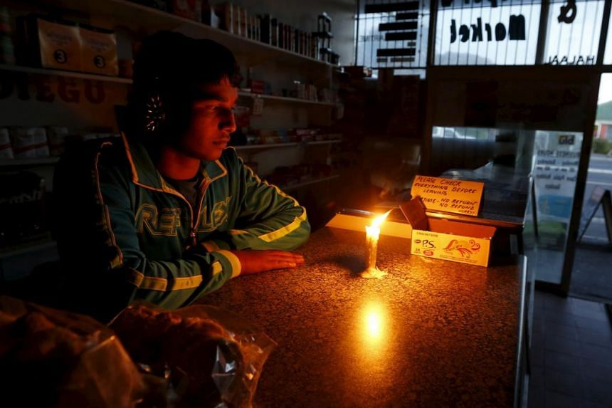 A shopkeeper in Cape Town waiting for customers during a load-shedding electricity blackout, done to prevent a grid collapse, on April 15. The current blackout crisis has been dragging on for several months.
