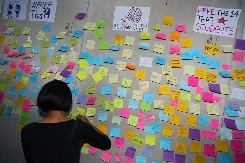 A supporter of Thai pro-democracy students writing messages to express support for the 'Post Freedom' campaign.