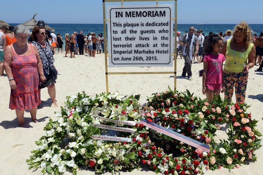 Tourists and Tunisians take part in a ceremony in memory of those killed.