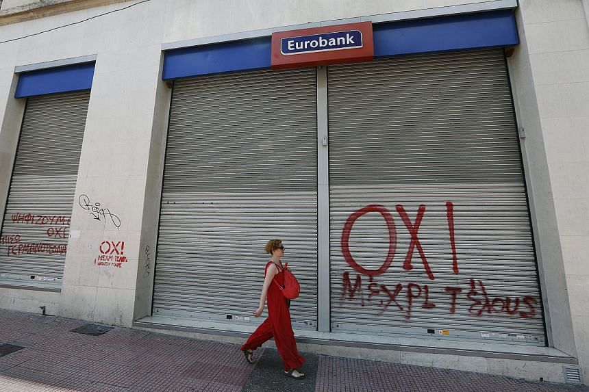 A woman walks by a closed Eurobank branch spray-painted with a NO graffiti in Athens, Greece on July 4, 2015.