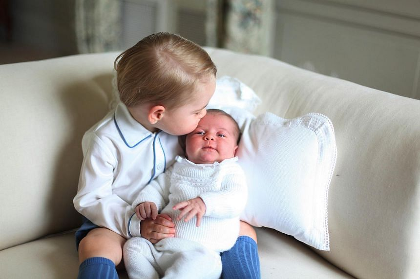 Prince George of Cambridge (left) gives a kiss to his sister Princess Charlotte in this picture released by Kensington Palace that was taken by Britain's Catherine, Duchess of Cambridge in May 2015.